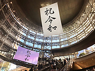 "May 2, 2019, Tokyo, Japan: As Japan entered the Reiwa Era, the Roppongi Hills development project with it's office tower, shops, restaurants, theaters and museum ushered in new era by displaying a giant banner with the kanji characters ""Shuku Reiwa"" (Celebrate Reiwa) above it's main entrance. A jumbro screen also occiasionally dispalyed the same message. Japan's Emperor Akihito abdicated the Chrysanthemum Throne bringing an end to the Heisei Era (1989 - 2019). The new era called 'Reiwa"" began May 1, 2019 when Crown Prince Naruhito ascended the throne. The two kanji characters ""'rei"" and ""wa"" can be translated as ""fortunate harmony"" or ""peace in harmony"" were taken from a stanza about plum blossoms in Man'yoshu, a collection of Japanese poetry written sometime after 759. Japanese calendars years are based upon the reigns of it's emperor's. Photo by Torin Boyd."