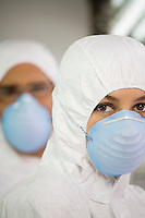 Workers in protective masks and suits portrait close up