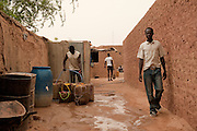 African migrants in a ghetto in Agadez. One of them is filling tins with some water.