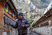 Man turning prayer wheels in Manang (Nepal)