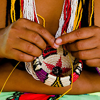 A young emberá female makes a basket, are one of the many typical craft made by the Emberás.  The Emberás are one of the seven indigenous groups still present in Panama.  They are usually find by the Chagres River in the Panama Canal protected areas as well as in the mountains and rivers of the Darien jungle