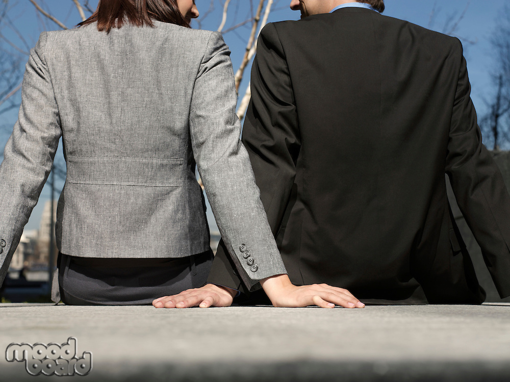 Business man and woman sitting on wall outdoors back view (cropped)