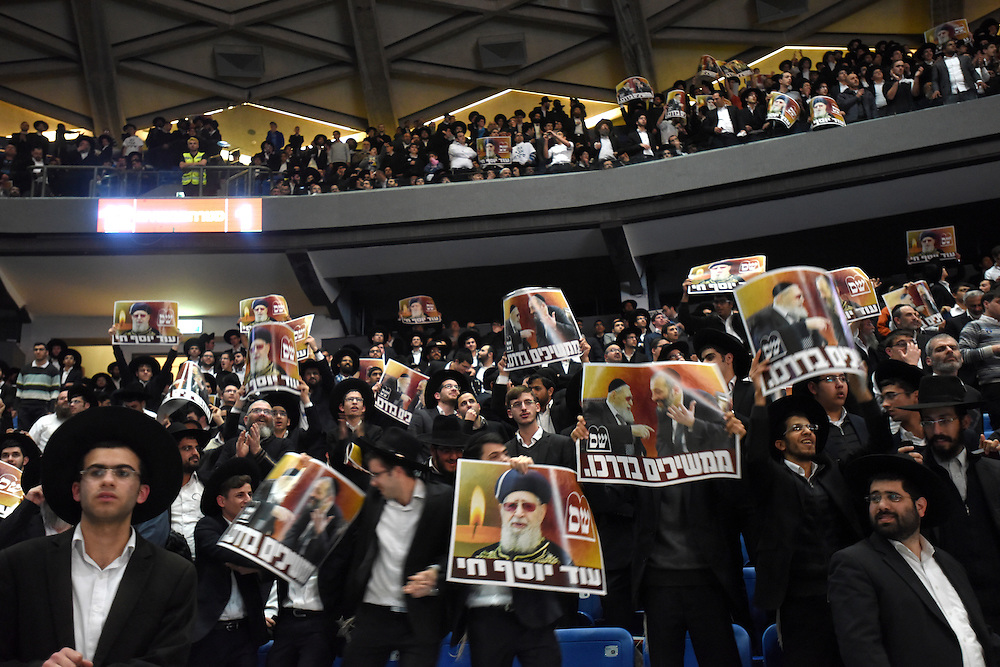 Ultra-Orthodox jews, supporters of Shas Party hold  pictures of the late Rabbi Ovadia Yossef during the party's rally in  Tel Aviv, March 3, 2015. Some 10,000 supporters of the Ultra-Orthodox Shas Party gathered on the Nokia Stadium in Tel Aviv for the party's election campaign largest rally. Photo by Gili Yaari