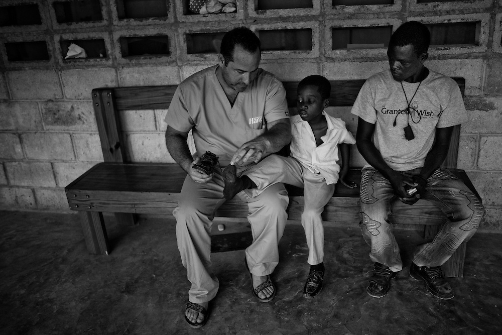 Jay Tew of the Hanger Clinic helps Gustav (6 yrs.), a below the knee amputee, put on his shoes.  After further inspection, Jay discovers that the shoes were already to small for Gustav and gave him a new pair.  Gustav and his mother travels hundreds miles to the clinic to get treatment.<br /> <br /> Hanger Clinic in Deschapelles, 120km from Port Au Prince, had provided artificial limbs to more than 500 earthquake victims.  The clinic also employs Haitians with few foreign specialists who volunteers two weeks at a time.  On average, the clinic helps 40 patients per day with prosthetics, physical therapy, adjustment and repairs, and counseling for free. Their funding and support comes from Hanger Orthopedic Group, Hanger Ivan R Sabel Foundation, Hospital Albert Schweitzer (HAS) and private donations.  Many patients travel hundreds of miles to the clinic to get treatment.  The clinic arranges transportations and offers lodging for patients needing to stay longer.