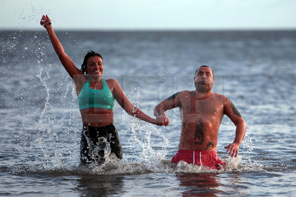 Licensed to London News Pictures. 01/01/2013, Whitley Bay, North Tyneside, UK. Carly Williams with dad Dave Cass-Williams join hundreds of swimmers braving the freezing North Sea as they take to the water in the annual Panama Swimming Club New Year Swim at Whitley Bay. Photo credit: Adrian Don/LNPP