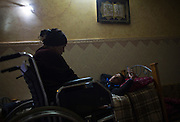 Wounded Palestinian woman  Asraah al-Namlah, and  her injured husband Wael in the evening as they listen to Arabic love songs in a room lit by safety lights during a power cut at their home in Rafa,Gaza January 20,2015. She lost both of her legs , and her son and husband each lost one leg  during last summer's war between Israel and the Hamas-controlled Gaza Strip. The incident happened on one of the darkest days during the war that has been named 'Black Friday'.Palestinians claim 130-150 were killed in the Rafa area of southern Gaza during a breakdown of a ceasefire agreement during a tunnel incident between Hamas and Israeli troops . <br />