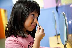 North America, United States, Washington, Bellevue, Girl (5 years) applying face make-up.  MR, PR