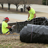 Adam Robison | BUY AT PHOTOS.DJOURNAL.COM<br /> Erick Morlina and Bernard Latusa, both from Slidell Louisiana and employees for RCI construction, install a slik fence on the grounds of the Elvis Presley Birthplace where work started on the phase 3 construction Tuesday morning in Tupelo.