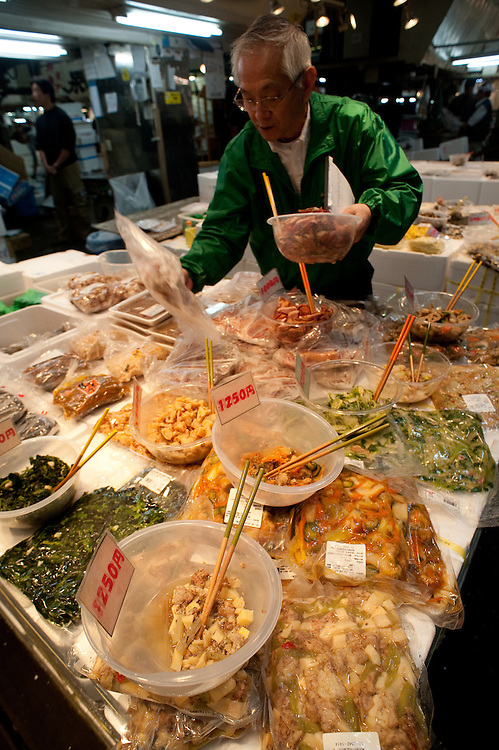 A foodseller arranges his prepared foods for sale.