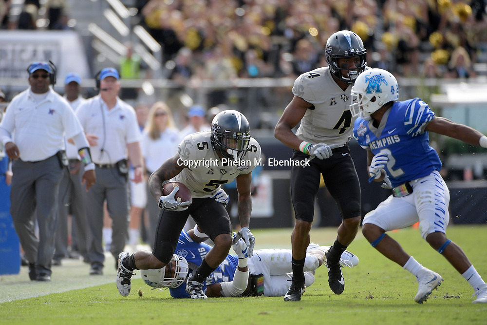 Central Florida wide receiver Dredrick Snelson (5) runs between Memphis defensive back Jonathan Cook (14) and defensive back Terrell Carter (2) after catching a pass during the first half of the American Athletic Conference championship NCAA college football game Saturday, Dec. 2, 2017, in Orlando, Fla. (Photo by Phelan M. Ebenhack)