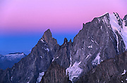 Twilight Wedge (Earth's shadow) cast behind the Peuterey Ridge of Mont Blanc 4808m (15,775ft). From left to right: Aiguille Noir de Peuterey 3772m (12,375ft), Les Dames Anglaises 3610m (11,844ft), Pointe Gugliermina 3893m (12,772ft) and the Aiguille Blanche de Peuterey 4112m (13,496ft).  Mont Blanc Group, Pennine Alps, Italy.  Nikon F4; 28-200/3.5-5.6.  Fuji RVP50.  Day 20 of l'Arc des Alpes (7 August 1998).