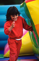 young girl playing hide and seek in bouncy castle inflatable
