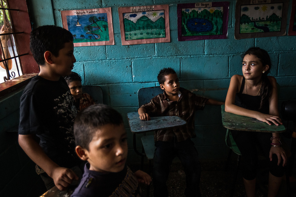 SAN PEDRO SULA, HONDURAS - MAY 23, 2014:  Children study at an elementary school in the La Pradera neighborhood, a Mara stronghold.  The police report that seven children have been murdered by Mara-18 gang members in this neighborhood in the past month, one as young as 7-years old.  PHOTO: Meridith Kohut for The New York Times