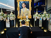 15 OCTOBER 2016 - BANGKOK, THAILAND:  A man signs a condolences book for Bhumibol Adulyadej, the King of Thailand, in EmQuartier mall in Bangkok. King Bhumibol Adulyadej died Oct. 13, 2016. He was 88. His death comes after a period of failing health. With the king's death, the world's longest-reigning monarch is Queen Elizabeth II, who ascended to the British throne in 1952. Bhumibol Adulyadej, was born in Cambridge, MA, on 5 December 1927. He was the ninth monarch of Thailand from the Chakri Dynasty and is known as Rama IX. He became King on June 9, 1946 and served as King of Thailand for 70 years, 126 days. He was, at the time of his death, the world's longest-serving head of state and the longest-reigning monarch in Thai history.     PHOTO BY JACK KURTZ