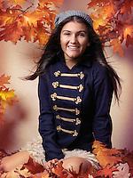 Smiling teenage girl sitting on fallen autumn leaves artistic fall fashion portrait