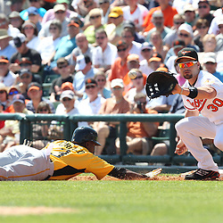 March 14, 2011; Sarasota, FL, USA; Pittsburgh Pirates shortstop Pedro Ciriaco (3) dives back before Baltimore Orioles first basemanLuke Scott (30) can make a tag during a spring training exhibition game at Ed Smith Stadium.   Mandatory Credit: Derick E. Hingle