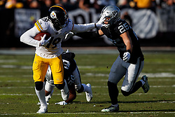 OAKLAND, CA - DECEMBER 09: Wide receiver JuJu Smith-Schuster #19 of the Pittsburgh Steelers stiff arms safety Erik Harris #25 of the Oakland Raiders during the second quarter at O.co Coliseum on December 9, 2018 in Oakland, California. (Photo by Jason O. Watson/Getty Images) *** Local Caption *** JuJu Smith-Schuster; Erik Harris