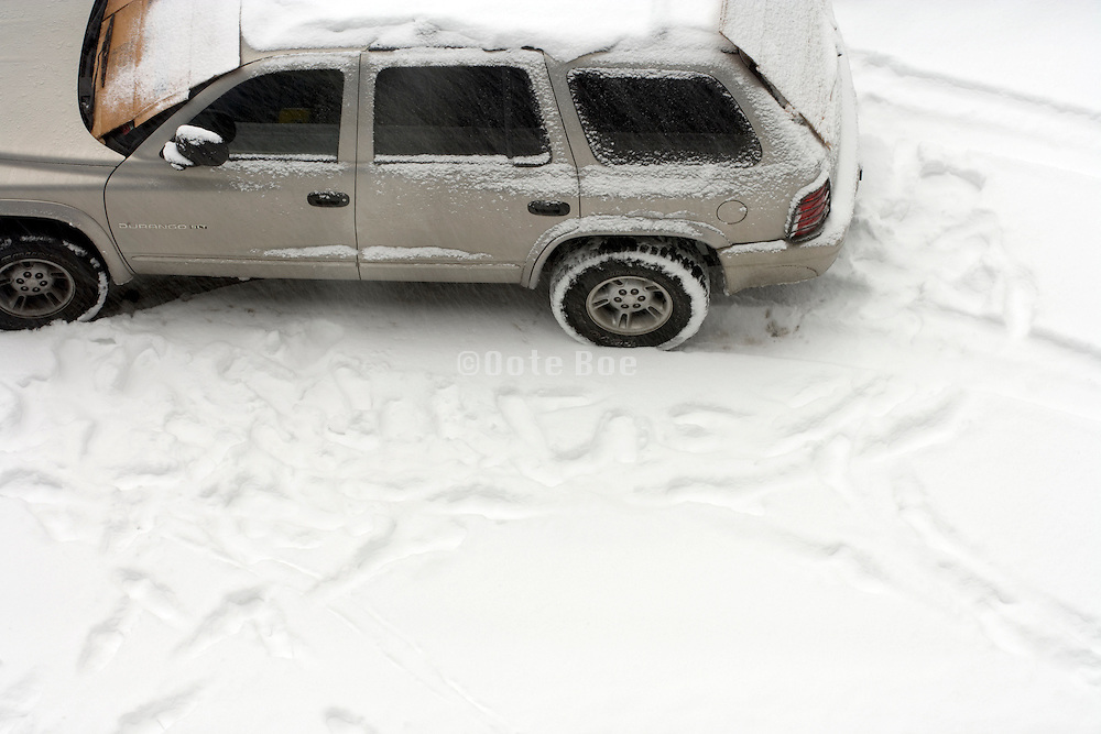 view from above of a parked car in the snow with footsteps around it