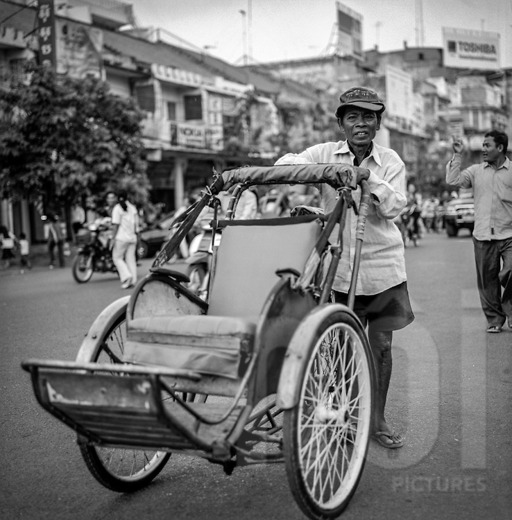 Cambodian cyclo driver near the central market in Phnom Penh waits for clients, Cambodia, 2005, Southeast Asia