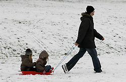 © Licensed to London News Pictures. 19/01/2013, London, UK.  A man pulls a sledge with children in a park in Croydon, South London, Saturday, Jan. 19, 2013. More cold weather and snow are expected over the coming days. Photo credit : Sang Tan/LNP