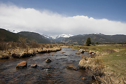 A swift moving stream flows through Moraine Park with snow capped Rockies in the background.  Rocky Mountain National Park (RMNP), founded by act of the US Congress in 1915, contains 72 named peaks above 12,000 feet in elevation including the tallest mountain peak in Colorado - Longs Peak at 14,259 feet.  The park, located next to Estes Park, CO, has five visitor centers and is traversed by the Trail Ridge Road (US highways 34 and 36).  Over 3 million visitors travel to the park annually to experience diverse mountain terrain, wildlife and recreation.
