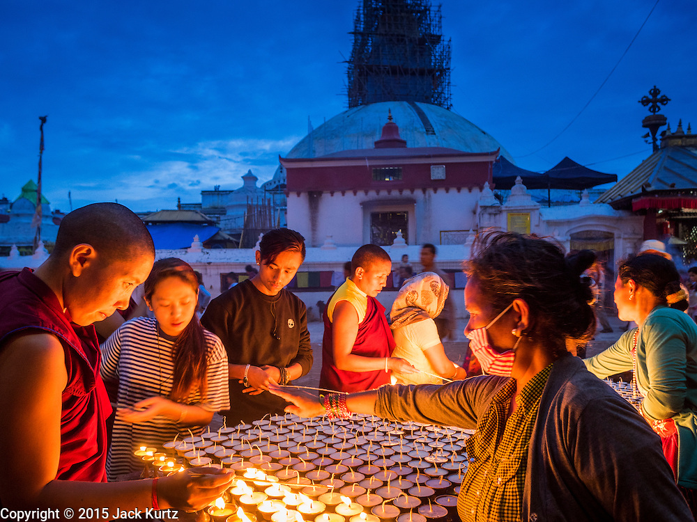 31 JULY 2015 - KATHMANDU, NEPAL:  People pray over butter lamps during the full moon processions at Bodhnath Stupa. Bodhnath Stupa in the Bouda section of Kathmandu is one of the most revered and oldest Buddhist stupas in Nepal. The area has emerged as the center of the Tibetan refugee community in Kathmandu. On full moon nights thousands of Nepali and Tibetan Buddhists come to the stupa and participate in processions around the stupa. The stupa was heavily damaged in the earthquake of 25 April 2015 and people are no longer allowed to climb on the stupa, now they walk around the base and pray with butter lamps.  PHOTO BY JACK KURTZ