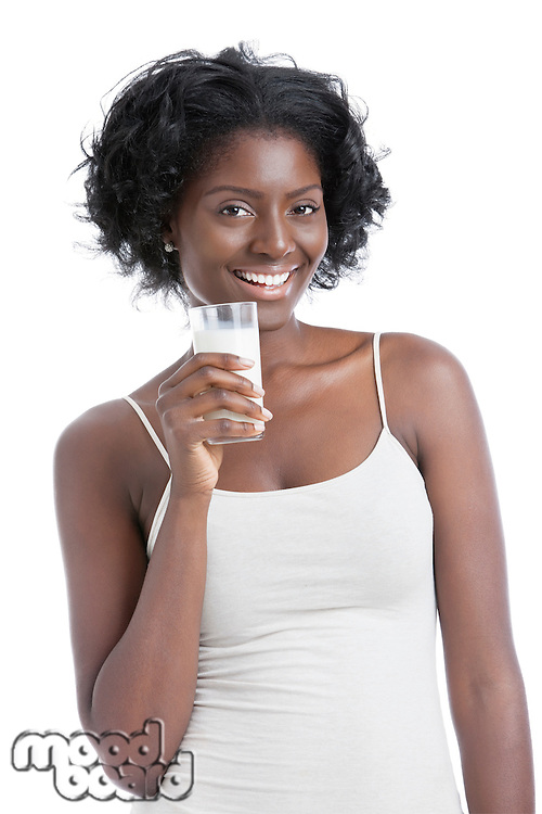 Portrait of happy young woman holding a glass of milk over white background