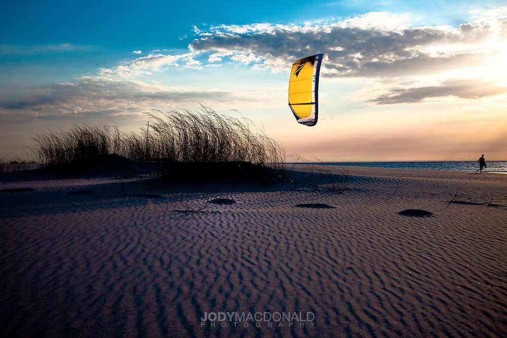 Kite and rider walk along sand with interesting clouds at sunset in mozambique