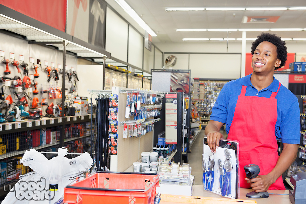 African American male store clerk at checkout counter in super market