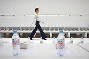 Girl model rehearses with bottled water at British couture designer Margaret Howell's Autumn fashion show in design studio