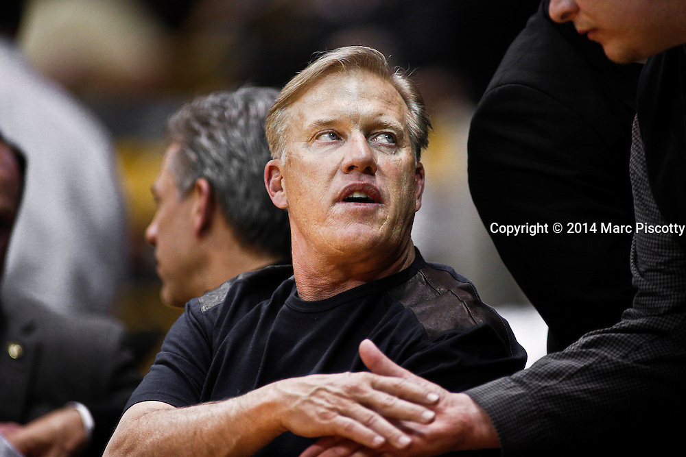 SHOT 2/19/14 10:57:54 PM - General Manager and Executive Vice President of Football Operations for the Denver Broncos John Elway shakes hands while watching Colorado play against Arizona State during the two teams regular season Pac-12 basketball game at the Coors Events Center in Boulder, Co. Colorado won the game 61-52.<br /> (Photo by Marc Piscotty / &copy; 2014)