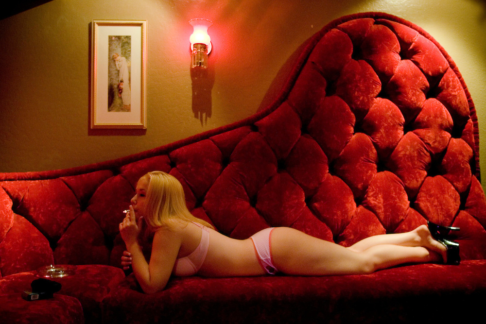 "Twenty-year-old sex worker Rhiannon relaxes in the parlor of the Moonlite Bunny Ranch brothel in Mound House, NV on Thursday, July 27, 2006...The Moonlite Bunny Ranch brothel in Mound House, Nevada - just a few miles from the state capital in Carson City - first opened in 1955. The Ranch is a legal, licensed brothel owned by Dennis Hof. It's featured in the HBO series ""Cathouse."""