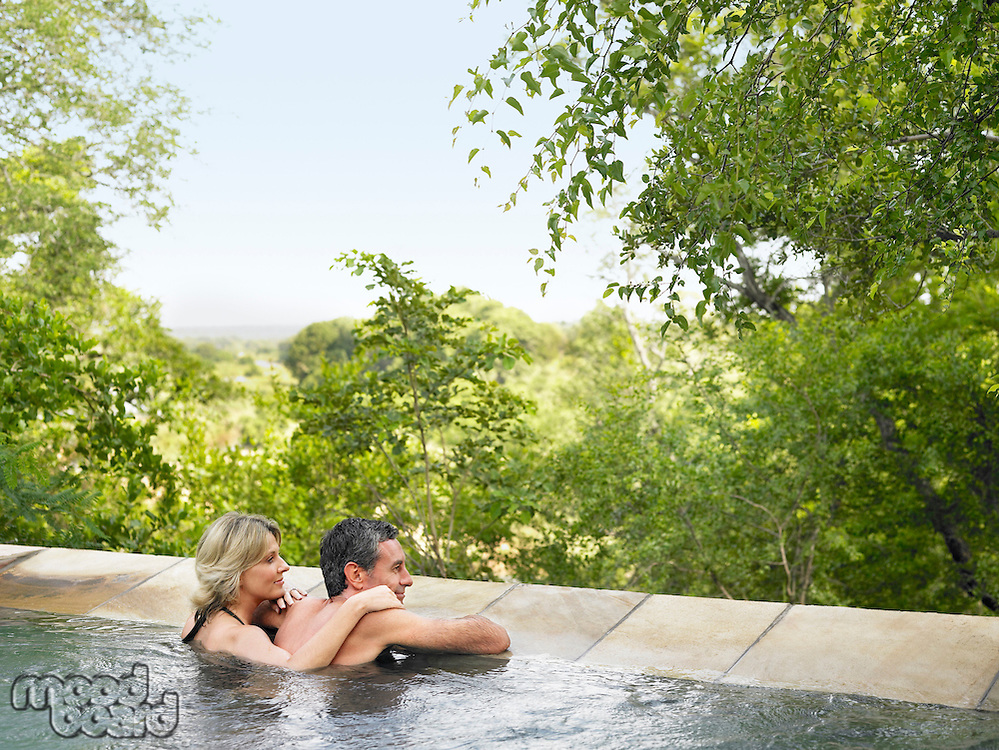 Adult couple in pool looking at view back view