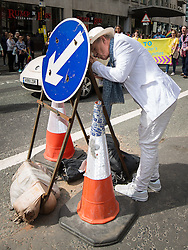 © Licensed to London News Pictures . 29/08/2015 . Manchester , UK . The actor , SIR IAN MCKELLEN , ducks behind a street sign to light a cigarette as he leads the 2015 Manchester Pride parade . Photo credit : Joel Goodman/LNP