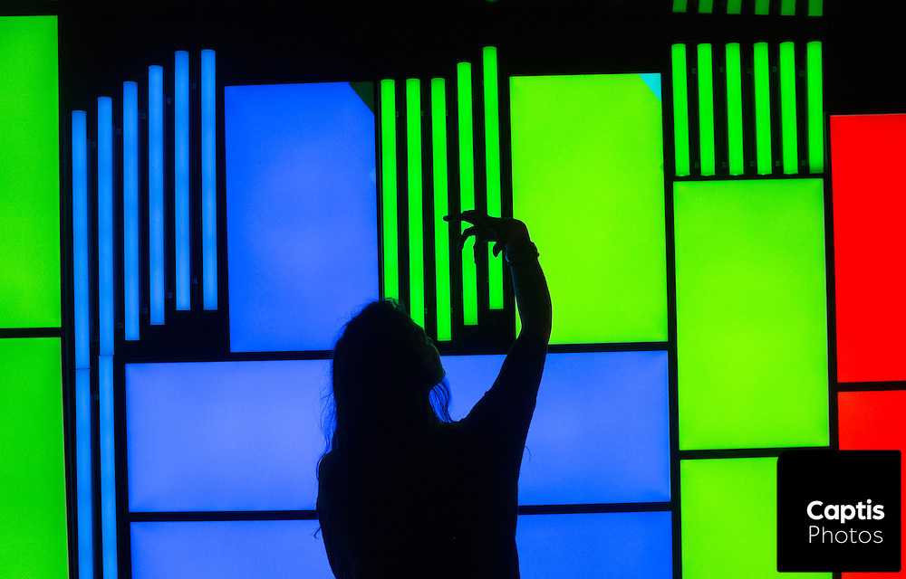 A woman poses for a photo in front of an abstract light screen. February 28, 2016 Brendan Montgomery/Captis Photos