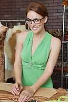Portrait of beautiful female fashion designer working in design studio