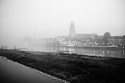 Het aanzicht van de Hanzestad Deventer gehuld in mist