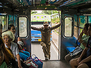 "13 MAY 2015 - MAHACHAI, SAMUT SAKHON, THAILAND: A State Railways of Thailand conductor in a ""songthaew"" running from Samut Sakhon to Samut Songkram. SRT sometimes uses songthaews as a shuttle when train lines are down for repair. The train tracks between Samut Sakhon and Samut Songkram are being rebuilt. Songthaew means literally ""two rows."" It is a passenger vehicle in Thailand and Laos adapted from a pick-up or a larger truck and used as a share taxi.    PHOTO BY JACK KURTZ"