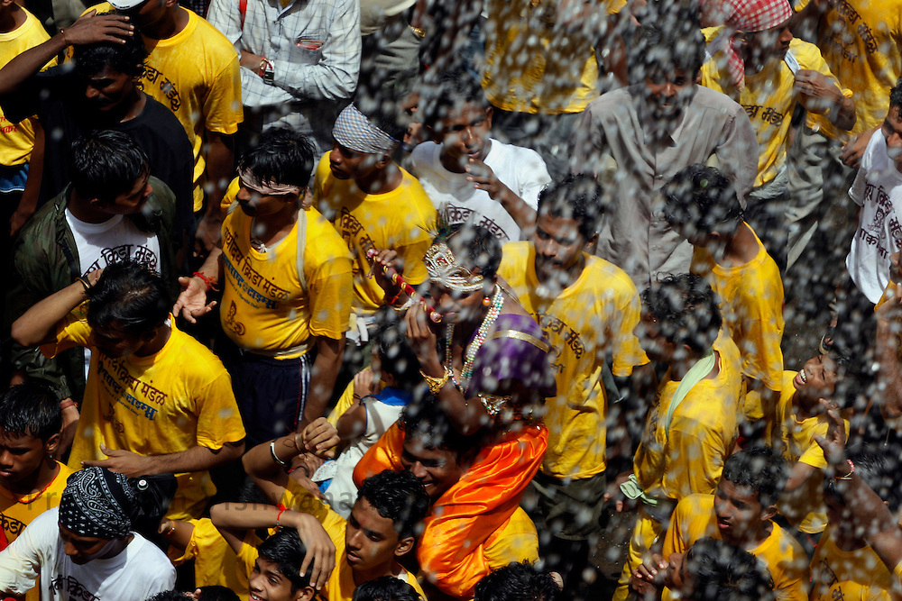 """A boy dresses as Lord Krishna as devotees attempt to break a pot containing butter on the occasion of  Krishna Janmashtami (birth of lord Krishna) in Mumbai, September 4, 2007. Janmashtami, which marks the birthday of Hindu god Krishna, will be celebrated across the country on September 4. As legend goes Lord Krishna as a child ate butter kept out of his reach by forming a human pyramid with his friends. Today these """"pots of butter"""" contain lakhs of Indian currency as prize money. People form multistoried layers and are ready to risk serious injuries. Photographer: Prashanth Vishwanathan"""