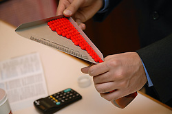 Pharmacist using dispensing triangle whilst preparing prescription,