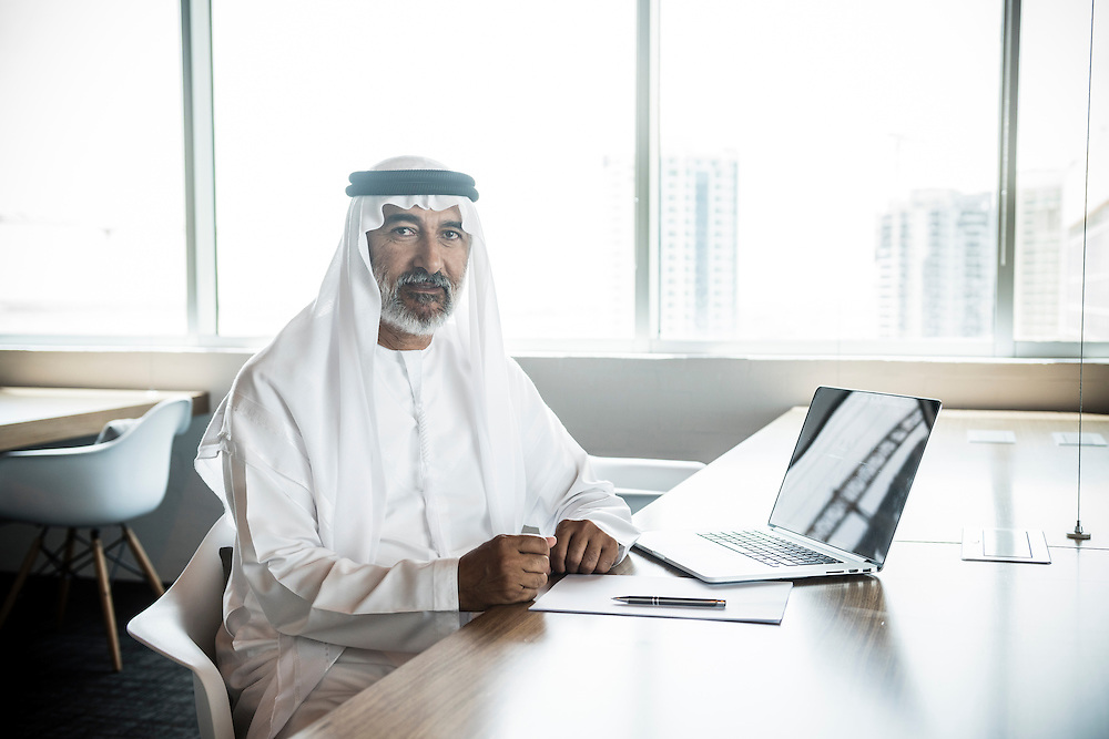 Portrait of a mature Arab businessman in traditional headress and kandura. Sitting at modern office desk with laptop computer, documents and window behind. Dubai, United Arab Emirates.