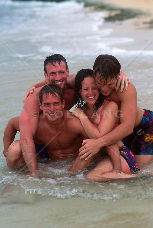 Four good looking friends in the water at the ocean