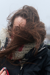 © Licensed to London News Pictures. 14/01/2020. Porthcawl, Bridgend, Wales, UK.  Student Jasmine from Bridgend goes out walking her dog Busterat Porthcawl in the Gale force winds which return to buffet the south Wales coastline following the arrival of Storm Brendan yesterday. Photo credit: Graham M. Lawrence/LNP