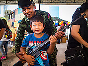 "14 JANUARY 2017 - BANGKOK, THAILAND: A Thai soldier helps a child hold an empty Royal Thai Army  M-16A1 assault rifle during Children's Day activities at the King's Guard, 2nd Cavalry Division base in Bangkok. Thailand National Children's Day is celebrated on the second Saturday in January. Known as ""Wan Dek"" in Thailand, Children's Day is celebrated to give children the opportunity to have fun and to create awareness about their significant role towards the development of the country. Many government offices open to tours and military bases hold special children's day events. It was established as a holiday in 1955.       PHOTO BY JACK KURTZ"