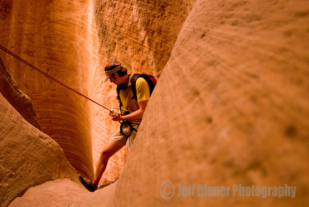 A young man rappels while canyoneering in Birch Hollow Canyon near Zion National Park, Utah.