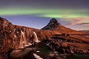 Aurora Borealis hoovering over mountain Kirkjufell in Grundarfjörður, Snæfellsnes peninsula, west Iceland. In foreground is waterfall Kirkjufellsfoss