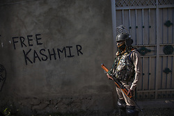 October 8, 2018 - Srinagar, Jammu and Kashmir, India - An Indian paramilitary trooper stands guard near the graffiti written on the wall of a polling station, during the first phase of municipal polls, in Humhama west of Srinagar.  (Credit Image: © Kabli Yawar/NurPhoto/ZUMA Press)