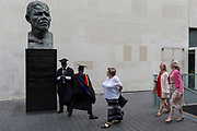 Young black graduates stand beneath the bust of Nelson Mandela after their graduation eremony, in celebration of their university academic achievement, outside the Festival Hall, on 20th July 2017, on the Southbank, London, England.
