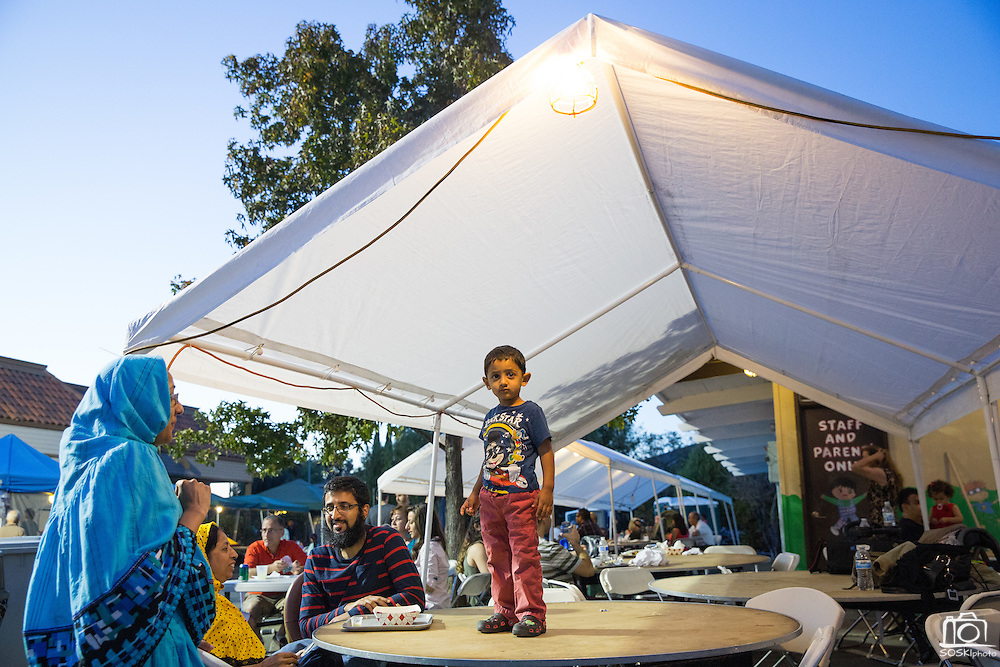Abdullah Kapadia, 2, stands on a table as revelers sing and dance during the Middle Eastern & Greek Food Fest at St. James Orthodox Church in Milpitas, California, on September 14, 2014. (Stan Olszewski/SOSKIphoto)