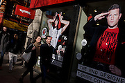 Shoppers walk beneath TK Maxx shop posters for the Red Nose Day charity, featuring Lily Allen and Dermot O'Leary.